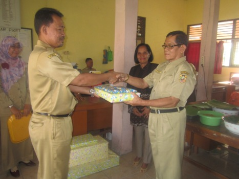 SELAMAT TINGGAL: Pak Siswanto (kiri) memberikan souvenir kepada pak Tiknyo