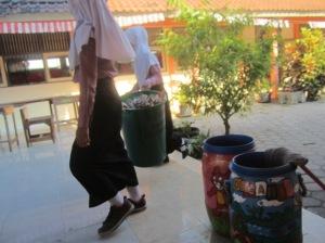 TERLAMBAT MASUK: dua siswi yang akan menuju ke TPA sekolah untuk buang sampah
