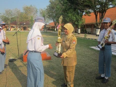 HARUMKAN SEKOLAH: Sherin (kiri) menyerahkan piala kepada Kepala Sekolah Dra. Endang Widarti, M.Par di sela-sela upacara bendera Senin (1/9) lalu.