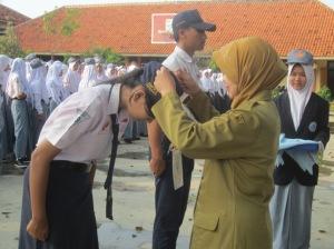 Pembukaan: Kepala SMAN 1 Cepiring Dra. endang Widarti, M.Par menyematkan tanda peserta dimuainya PLS (18/7).